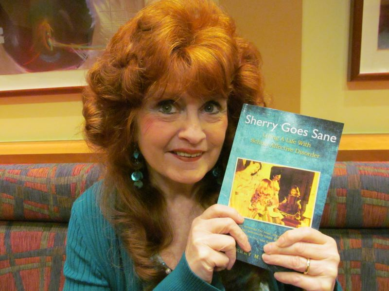 Sherry Joiner holds a copy of her recently released book 'Sherry Goes Sane.' The cover features a photo of her and her Aunt Deanna.