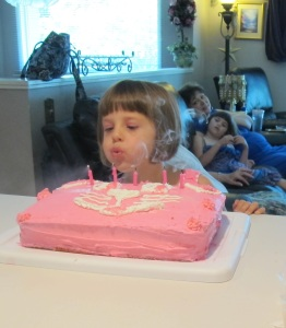 Kylie blowing out the candles on her birthday cake